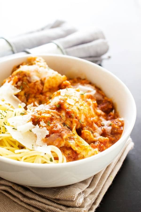 SLOW COOKER CHICKEN PARMESAN - A FAVORITE ITALIAN CLASSIC MADE EASY, WHILE TASTING JUST AS DELICIOUS.- white bowl, bran napkin, wooden table