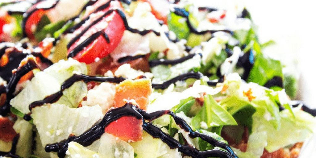 close up of chopped wedge salad with drizzled dressing