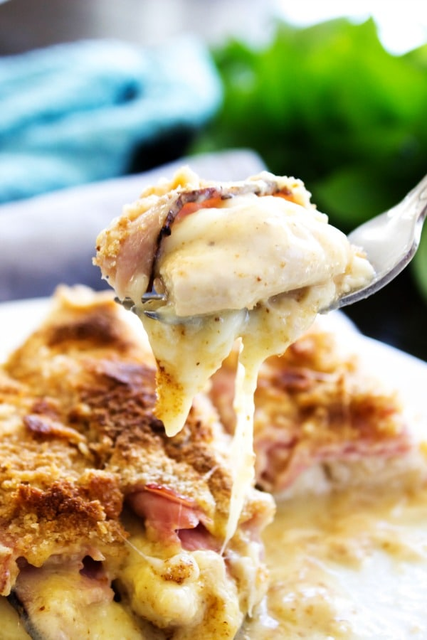 CREAMY CHICKEN CORDON BLEU CASSEROLE: White plate, metal fork, green plant in background