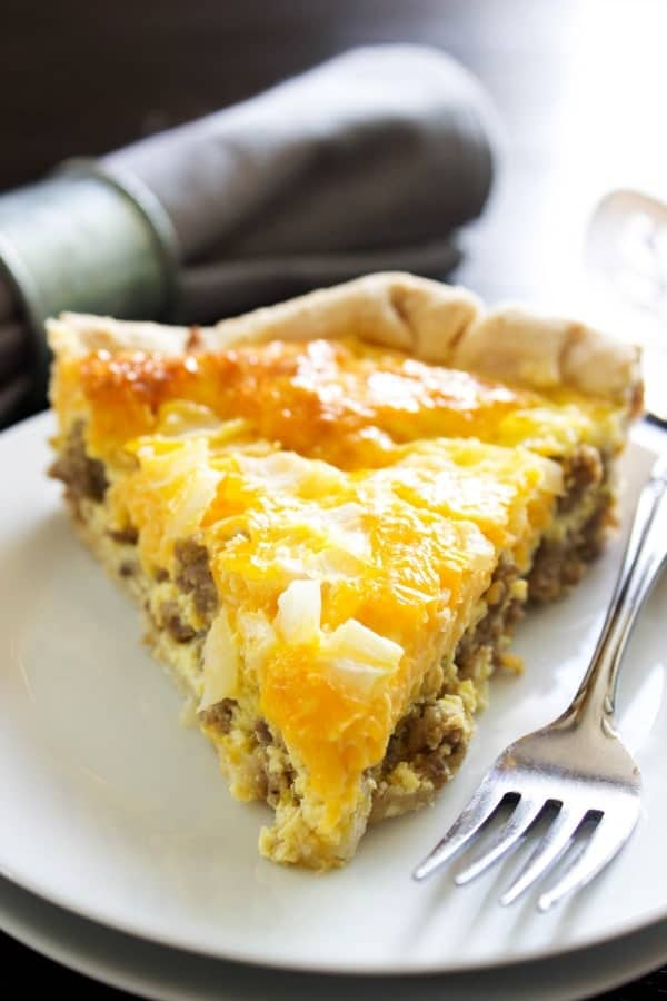photo of slice of easy sausage quiche on white plate with fork