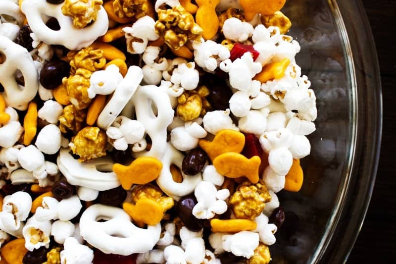 top down view of photo of Horsetooth Trail Mix in a glass bowl. popcorn, goldfish, yogurt pretzels, caramel corn, licorice pieces and chocolate covered raisins