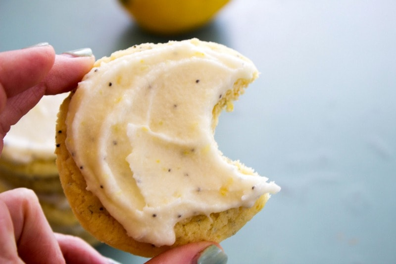 photo of a hand holding up a Lemon Poppy Seed Sugar Cookie with lemon buttercream, with a bite taken out