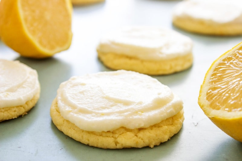 frosted lemon sugar cookies and cut lemons laid out on counter