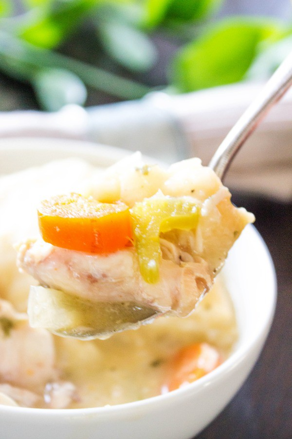 close up of a bite of chicken and dumplings on a spoon with bowl in background
