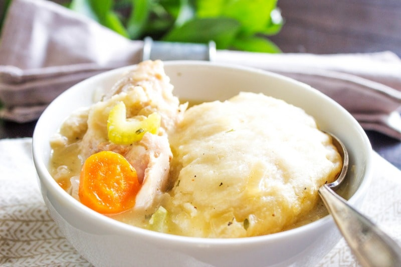 white bowl of chicken and dumplings with a metal spoon