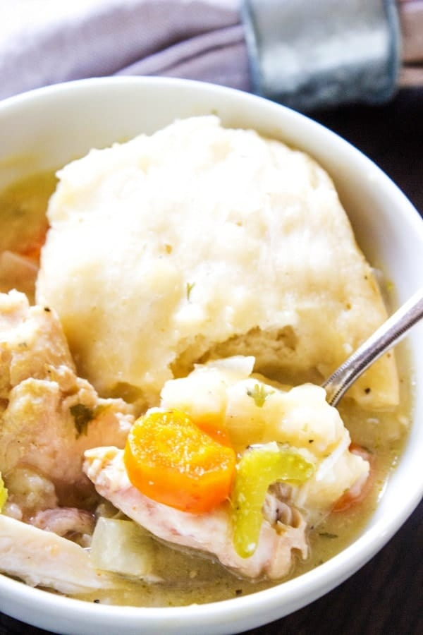 photo of chicken and dumplings oup in a white bowl with a spoon