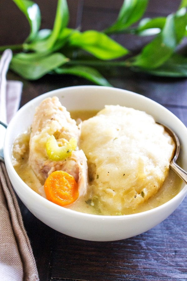 SLOW COOKER CHICKEN & DUMPLINGS in a white bowl with a spoon