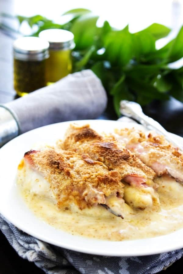 CREAMY CHICKEN CORDON BLEU CASSEROLE - Finished dish on white plate sitting on grey napkin, plant in the background