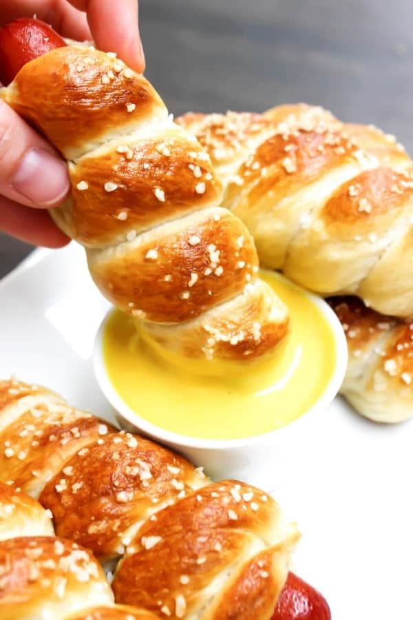 photo of pretzel hot dogs on a plate, dipping one into a small bowl of honey mustard sauce