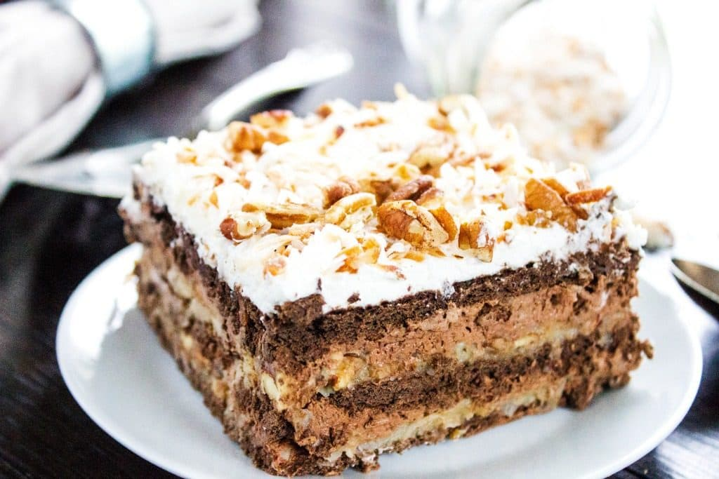 GERMAN CHOCOLATE ICEBOX CAKE - White plate, wooden table, metal work, grey napkin