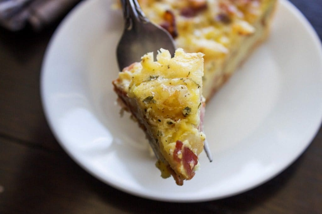 RANCH BACON POTATO QUICHE - White plate, metal fork, wooden table