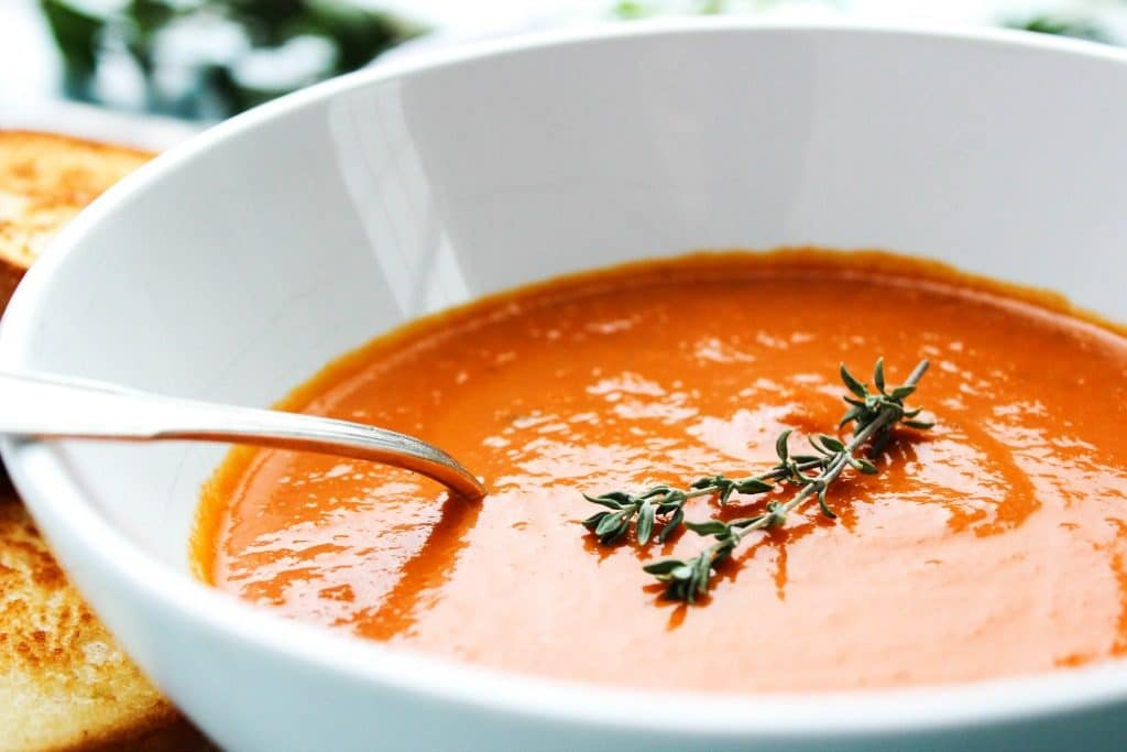 SLOW COOKER TOMATO SOUP - White bowl, metal spoon