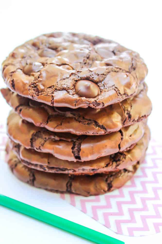 a stack of cookies on paper with a green straw