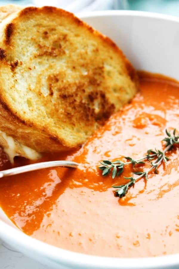 SLOW COOKER TOMATO SOUP - Soup in white bowl, metal spoon