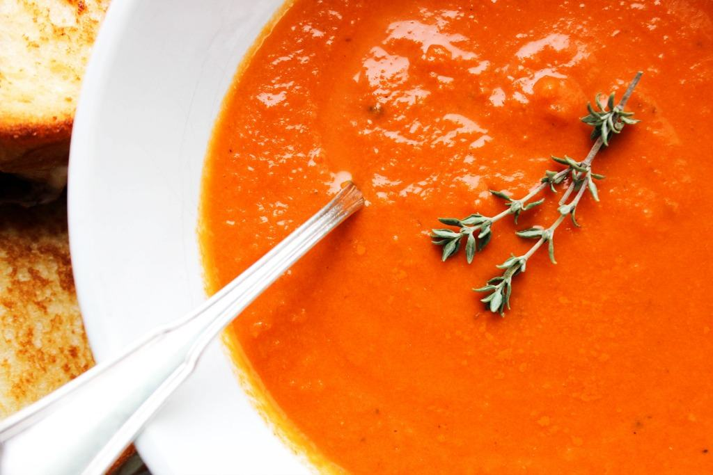 up close photo of tomato soup in a bowl with a sprig of thyme