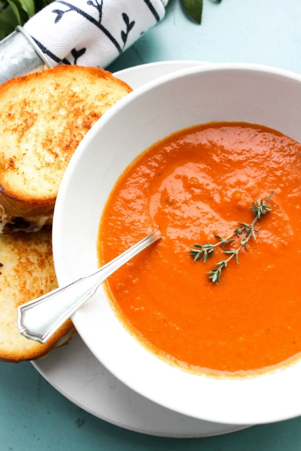 SLOW COOKER TOMATO SOUP -Metal spoon, white bowl and plate on blue table
