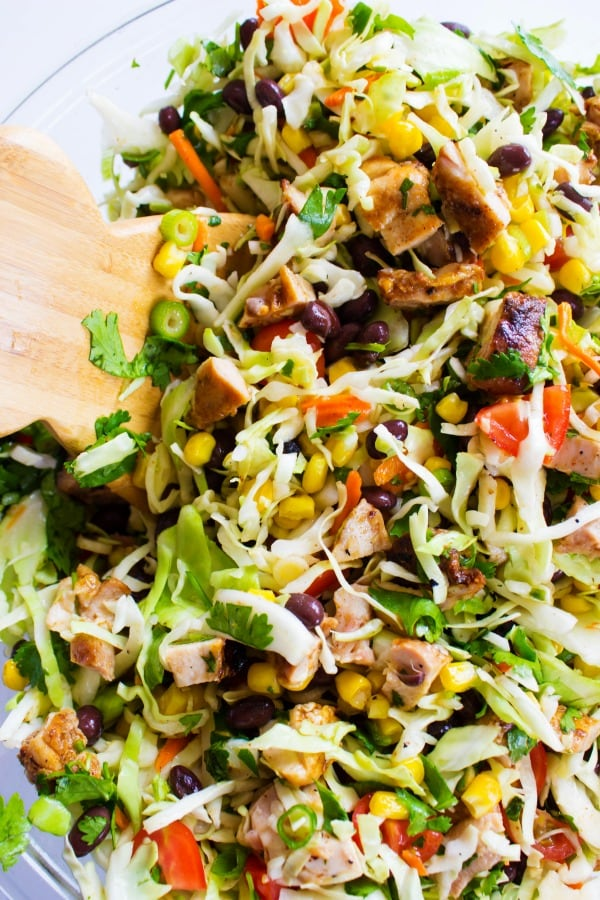 Chopped Southwestern Salad in a glass bowl with wooden salad tongs
