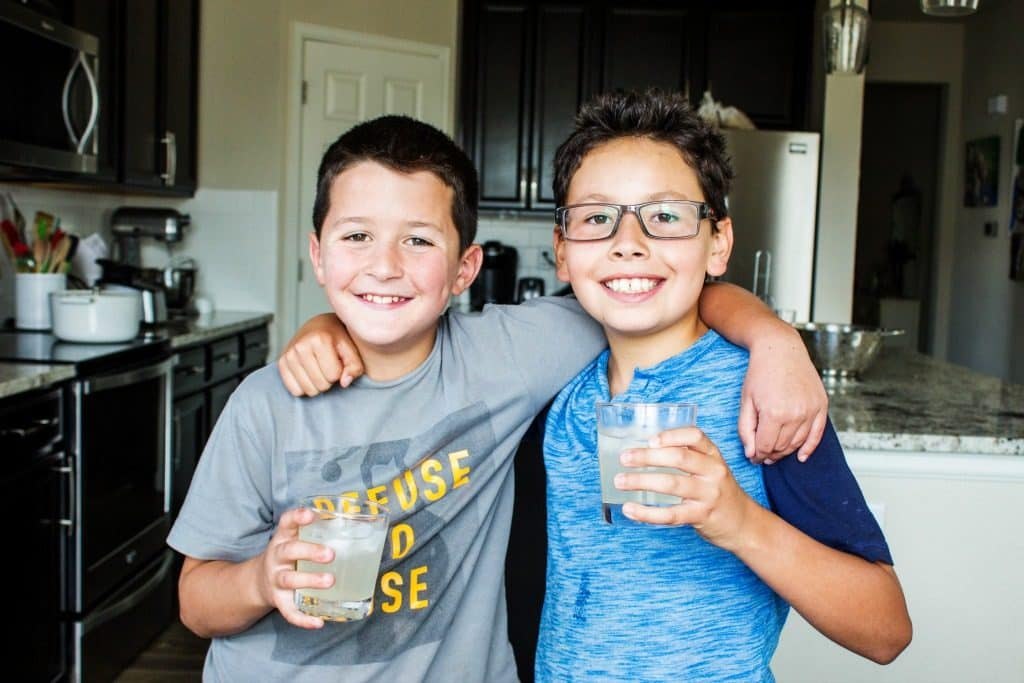 photo of 2 boys, Madden and Beni with arms around each other, drinking lemonade from glasses