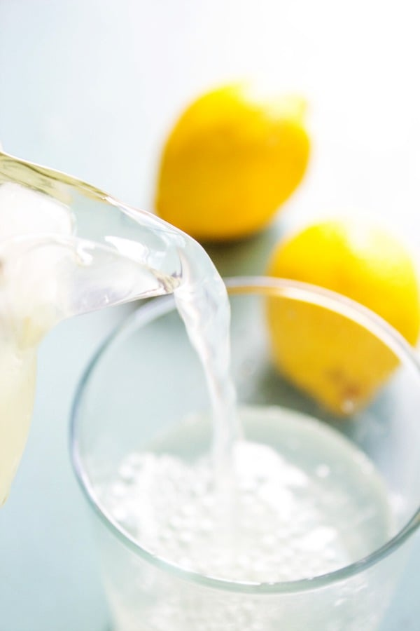 photo of pouring lemonade from pitcher into a glass, with 2 lemons on table in background