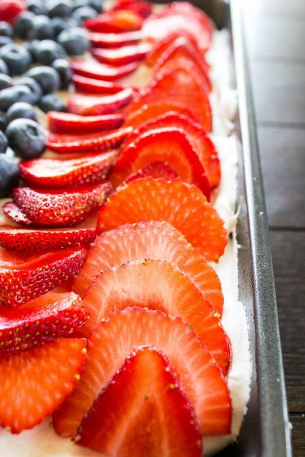This LEMON BERRY POKE CAKE Strawberries on cake in metal pan on wooden table