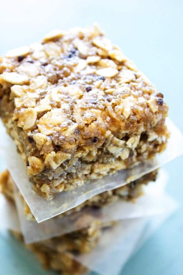 NO BAKE QUINOA & OAT BARS - Stacked with parchment paper on blue table