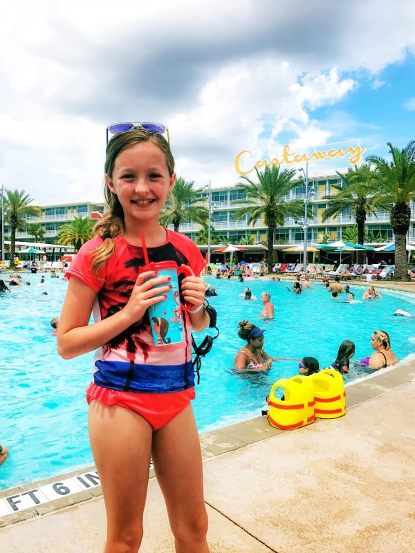 photo of girl in bathing suit at castaway resort pool holding refillable cup