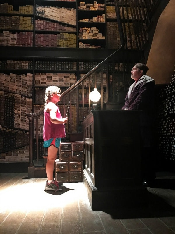 photo of girl holding a wand at ollivanders wand shop
