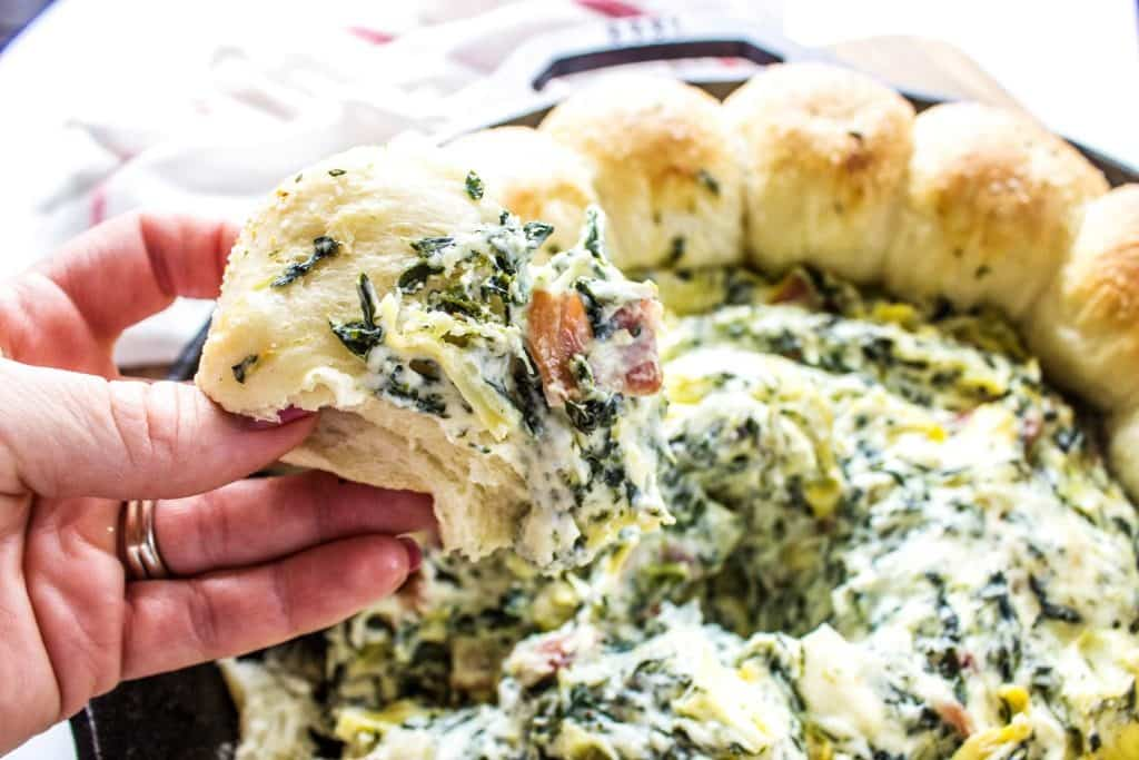 SPINACH ARTICHOKE BACON DIP RECIPE- Bite from dish displayed over iron skillet on a wooden cutting board