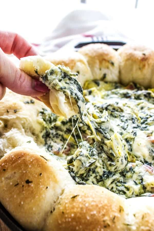 SPINACH ARTICHOKE BACON DIP RECIPE- Bite from dish displayed over iron skillet