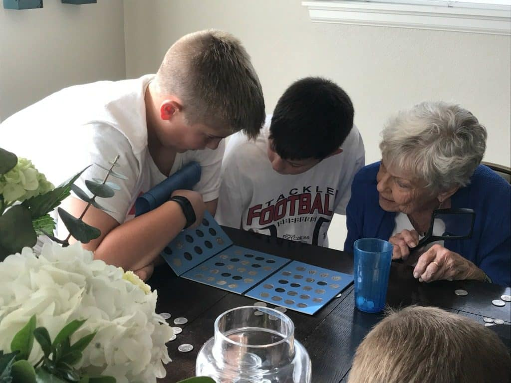 Sons Aiden and Madden with Grandma GiGi looking over coin collection