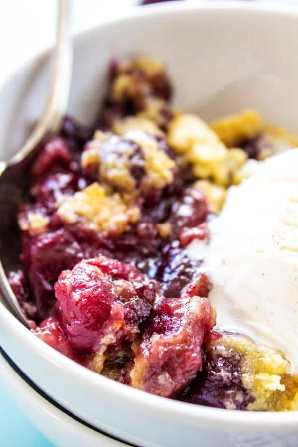 close up of cherry cobbler in a white bowl topped with vanilla ice cream