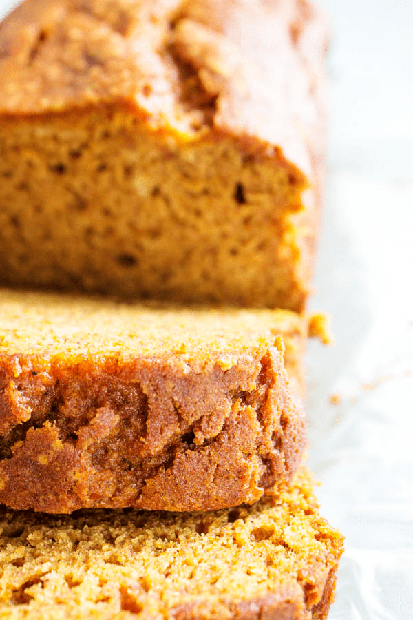 Close up of gluten-free pumpkin bread loaf with 2 pieces sliced