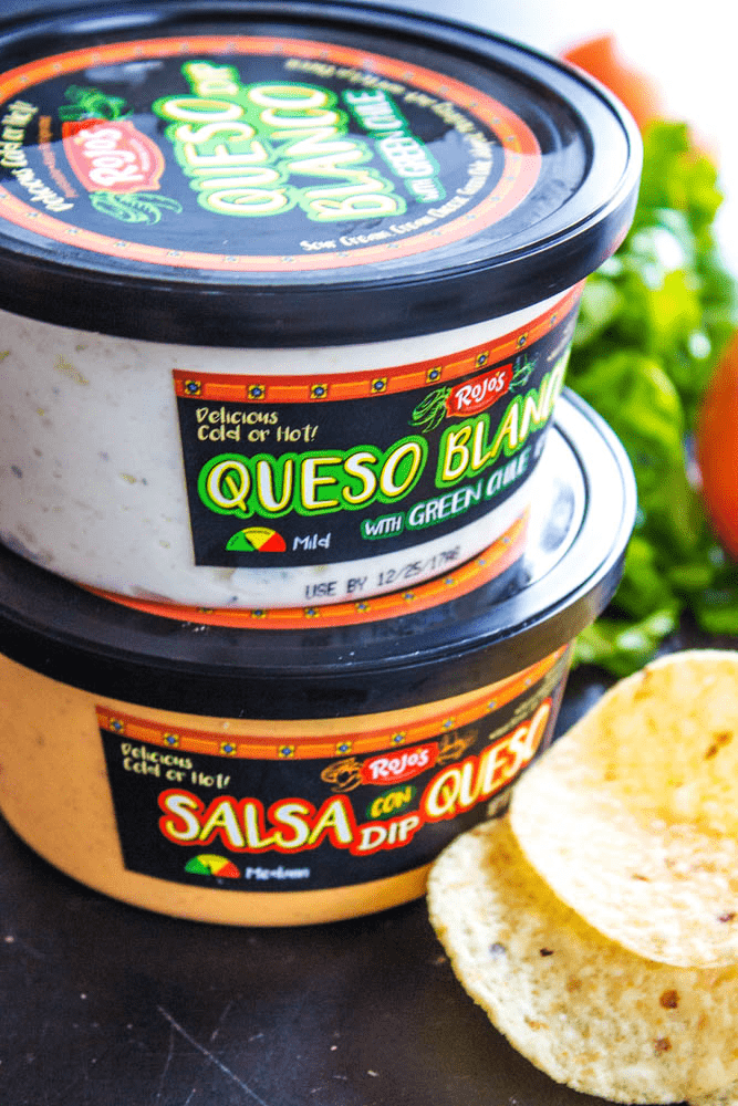 Queso Blanco and Salsa Con Queso dip containers stacked next to tortilla chips