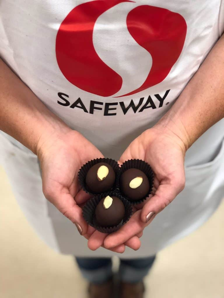 Safeway bakery employee holding 3 chocolate almond truffles