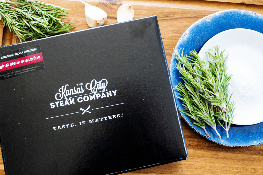 Kansas City Steak Company box with original steak seasoning packet enclosed, next to a plate with fresh rosemary and garlic