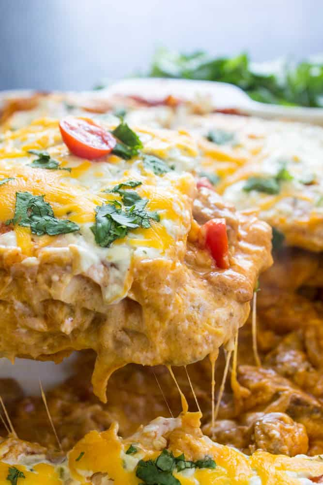 Steak and Queso Enchilada Casserole in baking tray with a serving being removed with a serving spoon