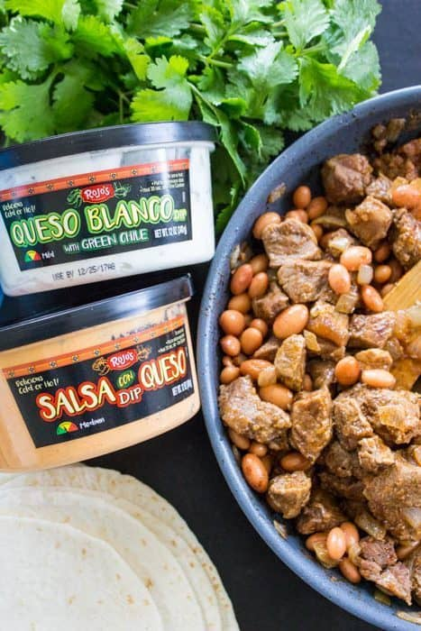 bowl with beans and steak next to a container of queso blanco and salsa con queso dips and tortillas