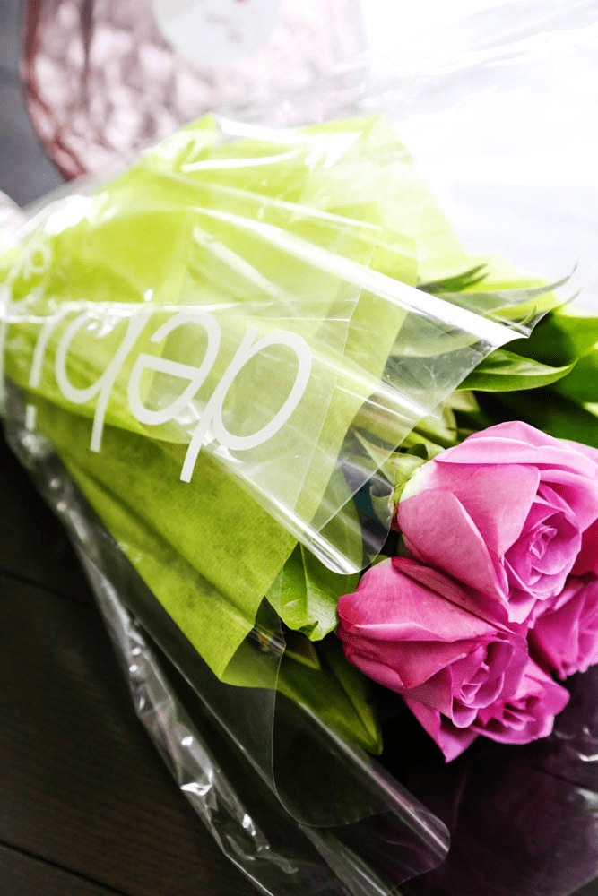 Bouquet of pink roses wrapped in cellophane and green paper