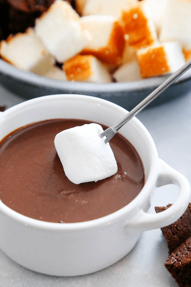 Chocolate Peanut Butter Fondue in a mug with a marshmallow on a skewer being dipped into fondue