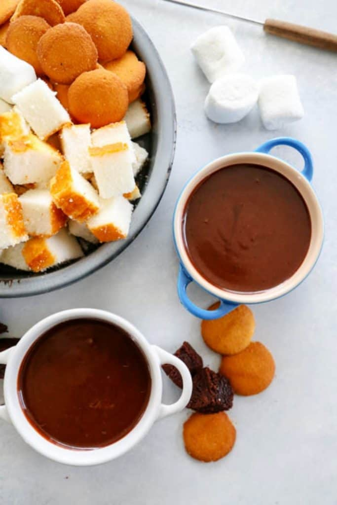 Chocolate Peanut Butter Fondue in 2 mugs next to a platter with small pieces of brownies, angel food cake, marshmallows, and nilla wafers