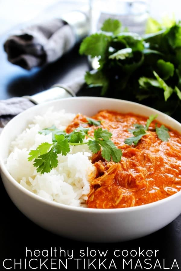 photo of tikka masala in a white bowl with rice and herbs