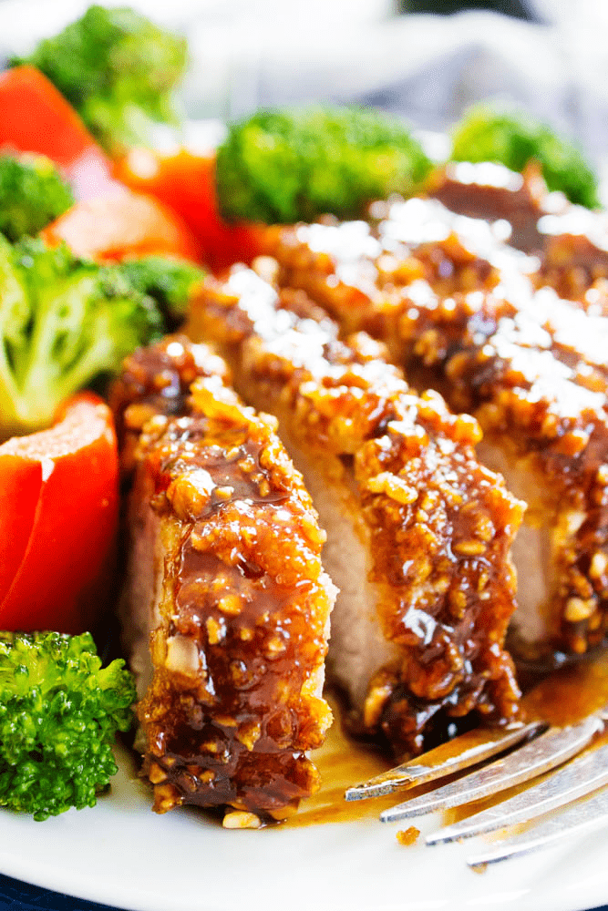 Cashew Oven-Fried Pork Chops sliced, served on a plate with broccoli and red peppers