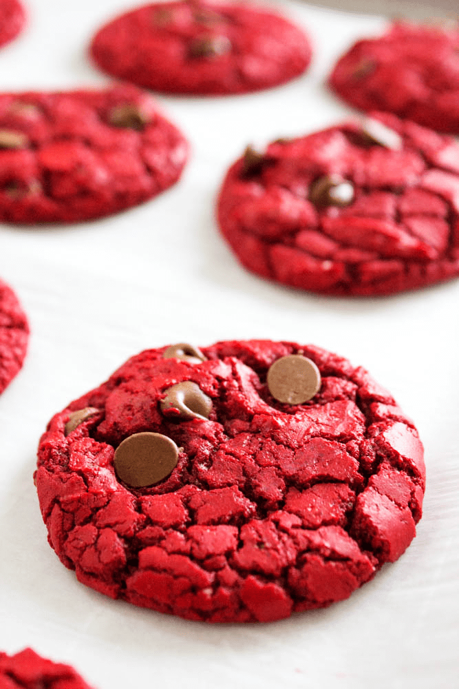 baked red velvet cookies on a sheet pan with parchment paper
