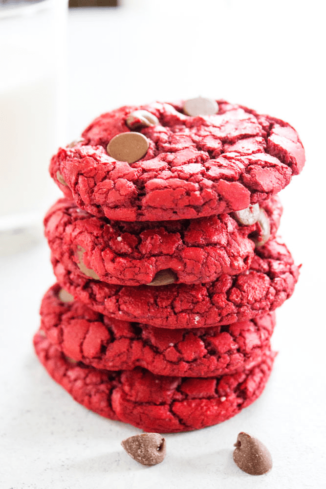 5 red velvet cookies in a stack with chocolate chips on counter