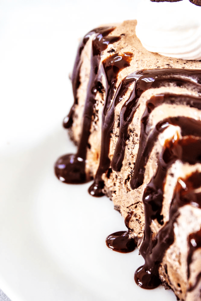 chocolate oreo ice cream cake, slice close up on a plate with hot fudge drizzle
