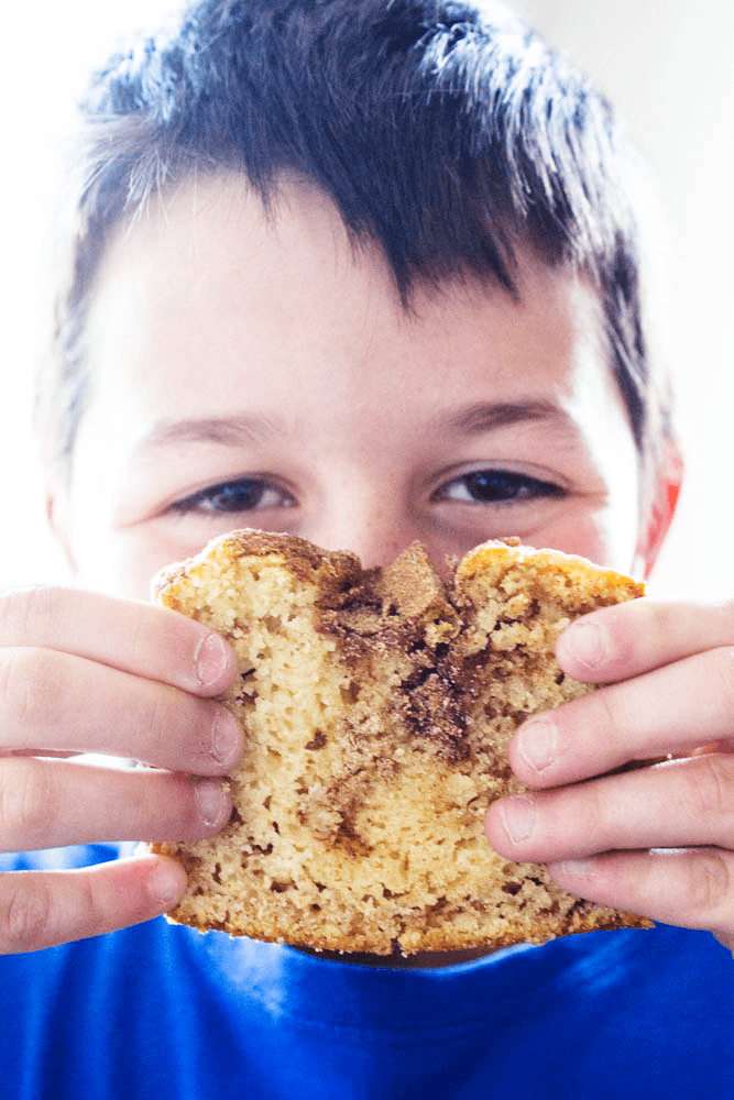 photo of boy holding slice of cinnamon sugar bread up to his face