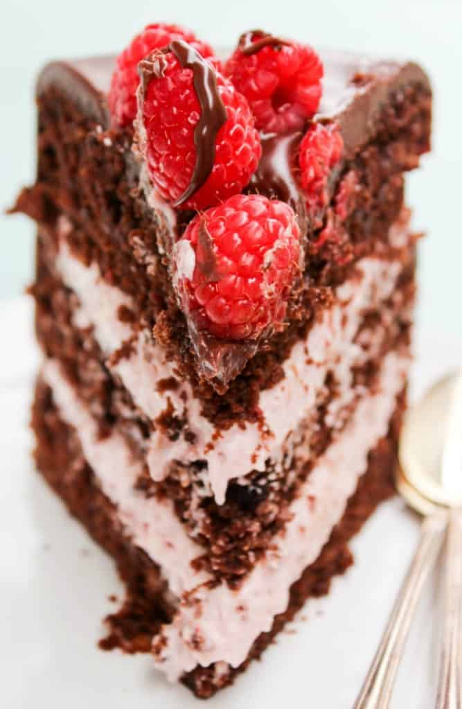 Photo of 3 layer chocolate raspberry cake slice with fresh raspberries on top