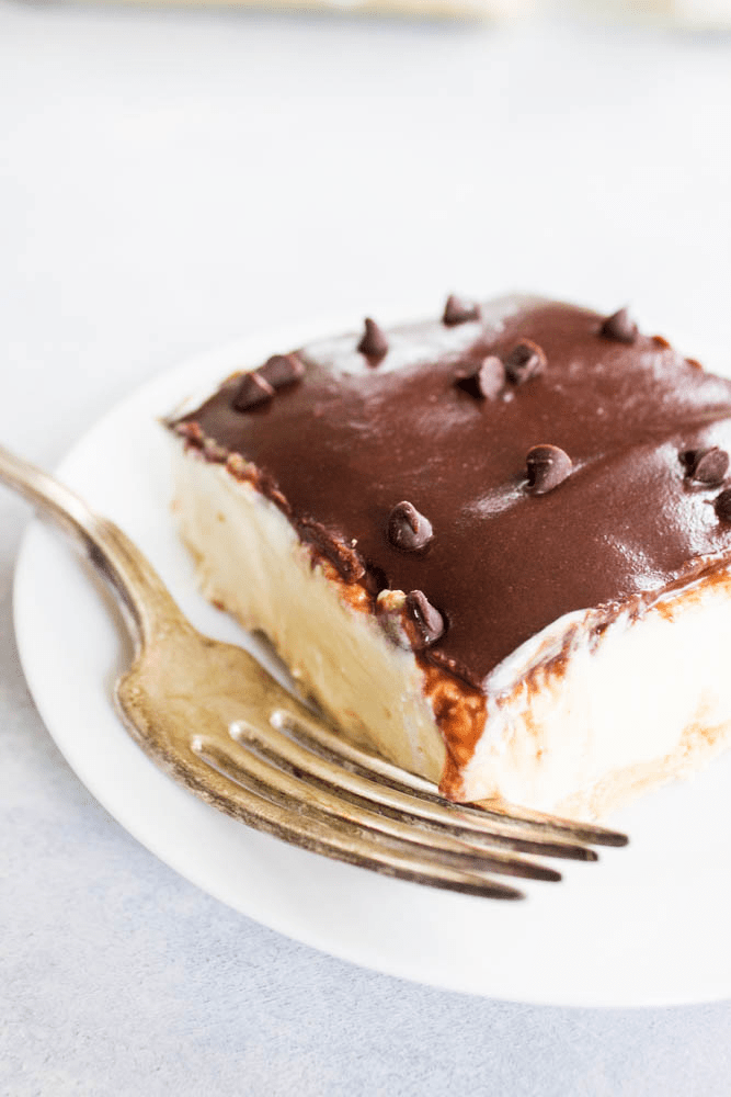 square slice of No-Bake Boston Cream Pie Cheesecake on a small plate with a fork