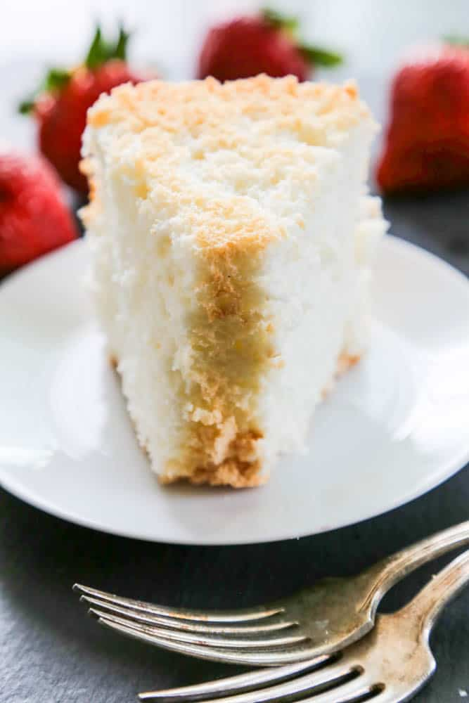 Angel Food Cake slice on plate with forks and strawberries whole in background