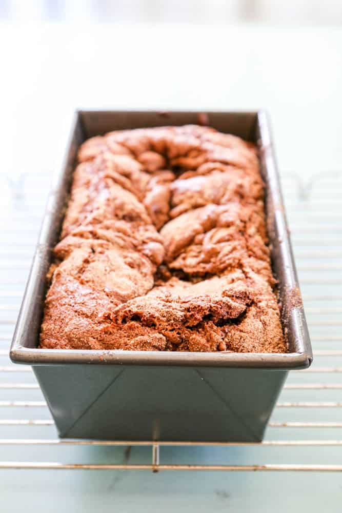 Chocolate Cinnamon Bread baked in metal bread pan on a wire rack
